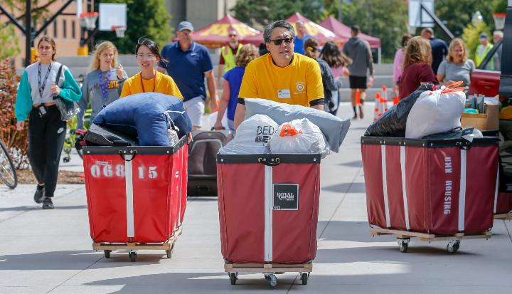 Regent Hsu pushing bins on student move-in day.